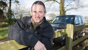 Farmer Simon Beddows leaning on a fence