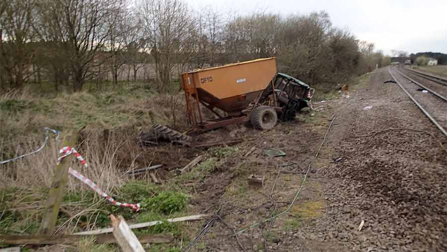damaged tractor and trailer beside railway line
