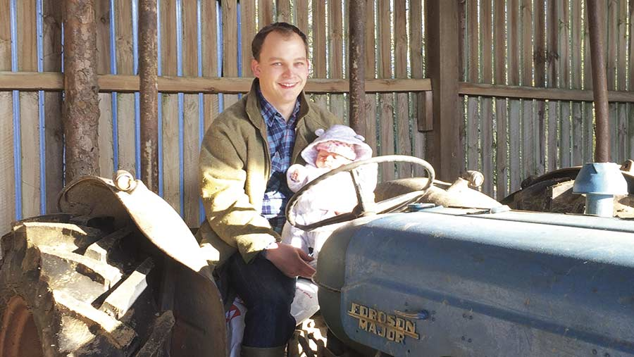Will Sargent sits on a tractor with his baby daughter Eve in his arms