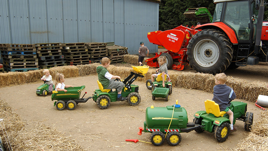 Children riding toy tractors on a farm