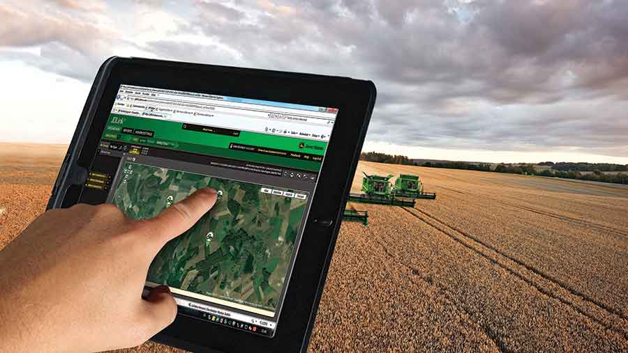 Hand typing on tablet in combine cab