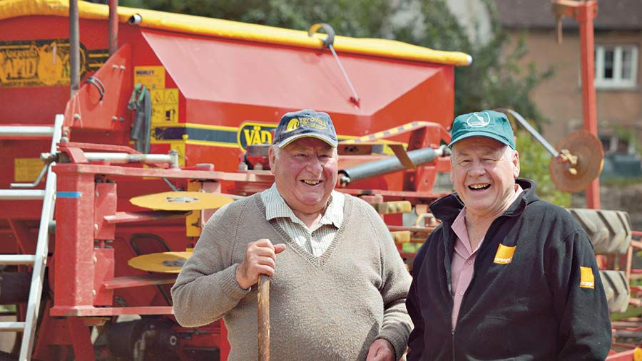 Julian Pickworth stands next to another man in front of farm machinery