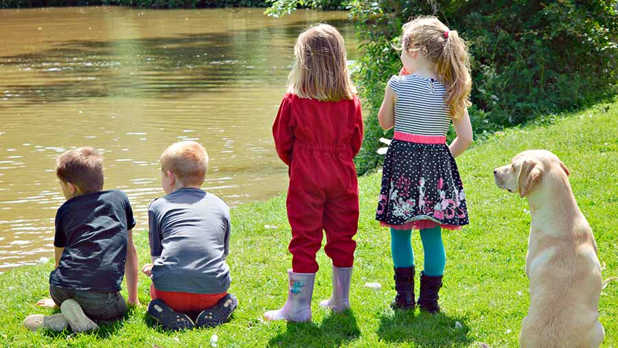 Children stand at the edge of a waterway