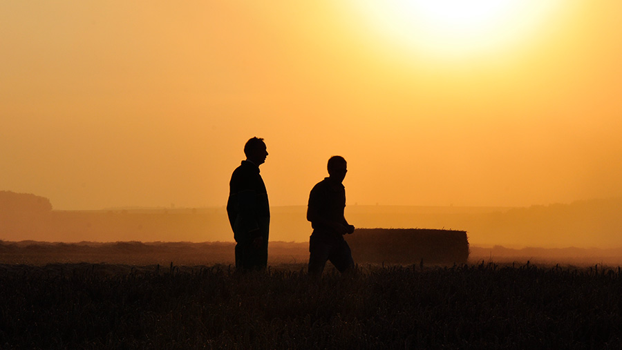 Silhouette of two farmers in a field at sunset