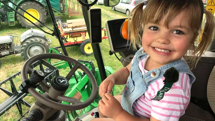 A young girl smiles as she sits in a tractor cab