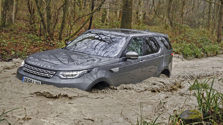 A Land Rover Discovery crosses a river