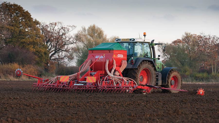 A tractor and seed drill in November, with bare trees