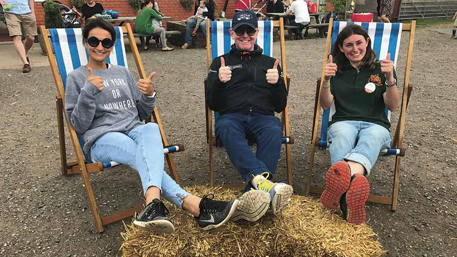 Radio 2 star Chris Evans sits on a deckchair with his feet on a straw bale. To his left is his wife Natasha Shishmanian and to his right is Alison Frost, Row Farm's OFS organiser. All three are giving the photograph a thumbs up sign
