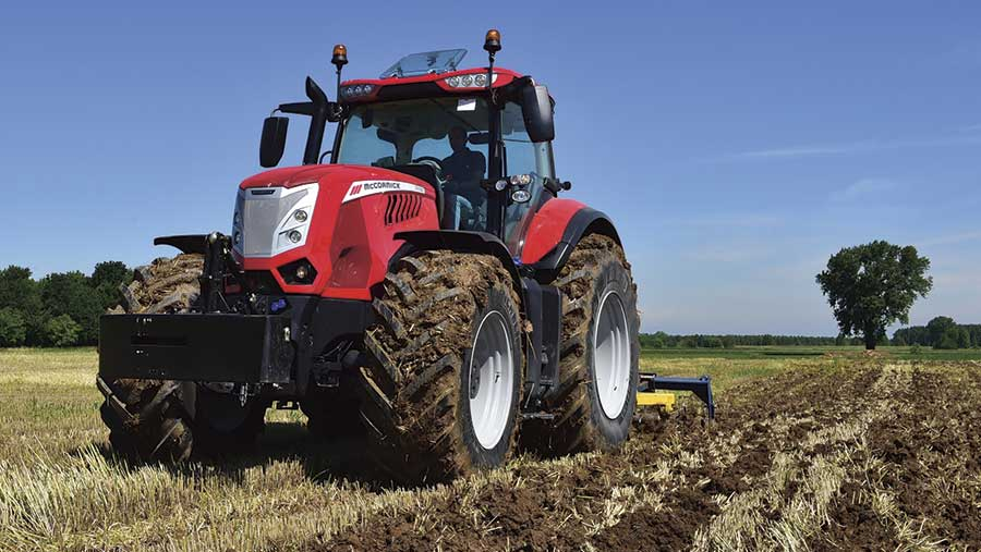 A red tractor cultivating a field