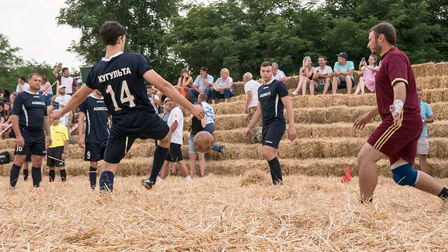 Men take part in a football match in a stadium made of straw