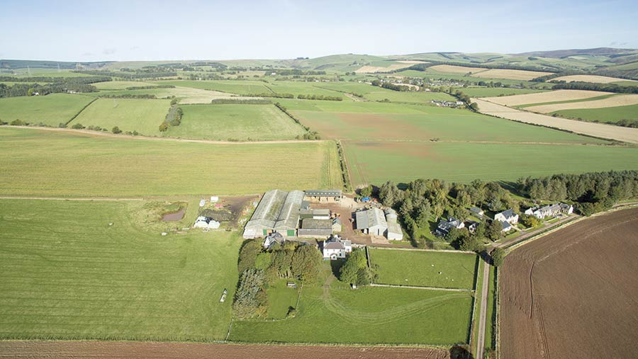 An aerial view of a farmhouse and farm buildings in green fields