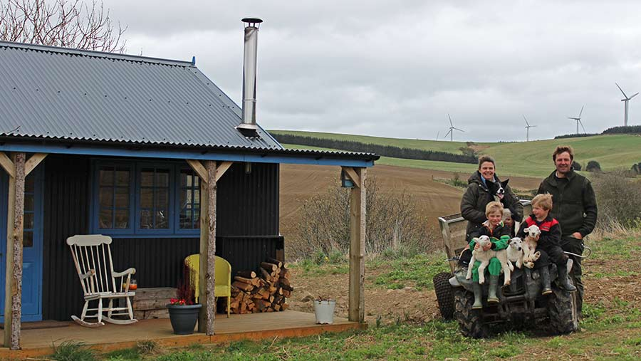 Jane Foad, husband James and two sons sit on a quad bike in a field. The boys hold three lambs