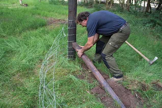 Man constructing fence